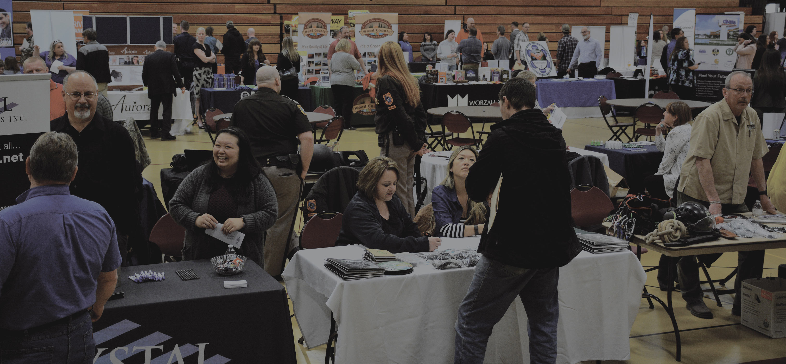 Job Fair taking place in Mid-State Technical College Gymnasium. 15+ tables set up in view with poster board and people walking around looking at job opportunities.