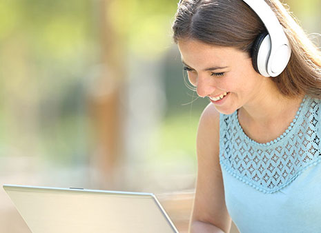 Woman sitting with headphones on looking at a laptop