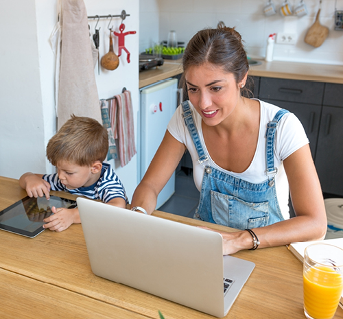 Woman sitting at a table looking at a laptop with a child sitting next to her looking at a tablet.