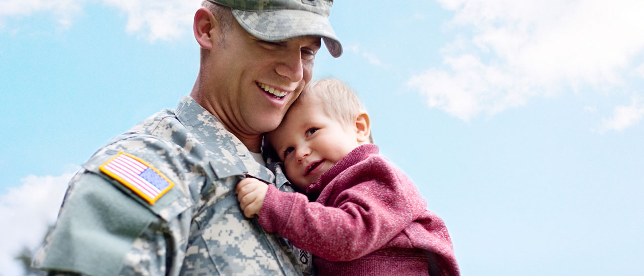 Man in uniform holding a child