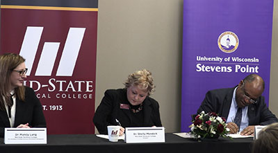 Dr. Shelly Mondeik, president of Mid-State Technical College, center, and Dr. Al S. Thompson, Jr., vice chancellor for student affairs and senior diversity officer at UW-Stevens Point, sign an agreement to provide housing for Mid-State students in a UW-Stevens Point residential living hall. The signing took place during an event formalizing the new partnership on Mid-State's Stevens Point Campus, Feb. 4. Also pictured, left, is Dr. Mandy Lang, Mid-State's vice president of student services & enrollment management.