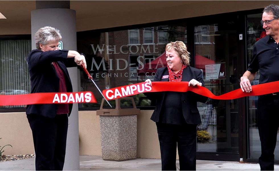 Campus Dean Laurie Inda cuts the ribbon on Mid-State Technical College's Adams Campus at the Oct. 1 ribbon cutting and open house event. Assisting her are Mid-State President Dr. Shelly Mondeik, center, and Mid-State Board Member and Treasurer Charles Spargo.