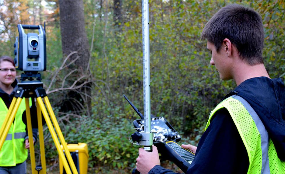Civil Engineering Technology-Highway Technician students Luke Mroczenski and Nicole Burdick survey a trail using a Trimble S7 robotic total station.