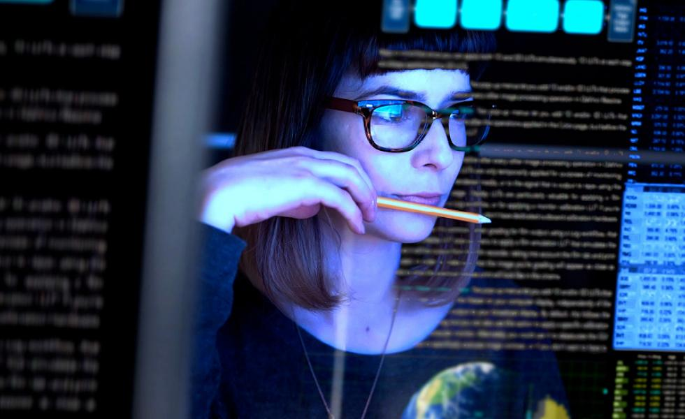 Female IT professional holding a pencil looks at a computer monitor displaying code and images