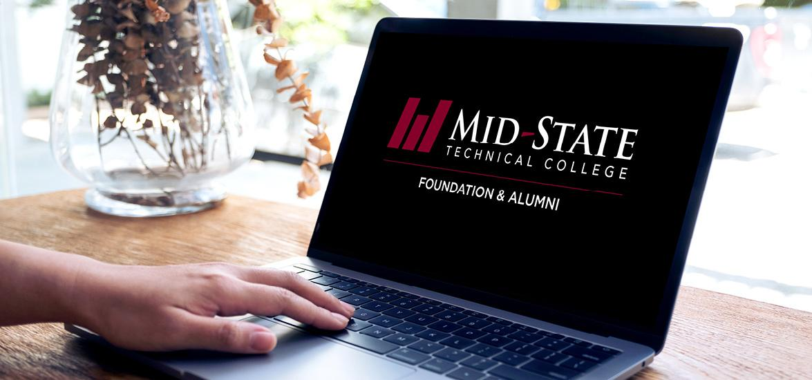 A laptop sitting on a desk with a hand resting on the keypad. The screen shows the logo for the Mid-State Technical College Foundation & Alumni.