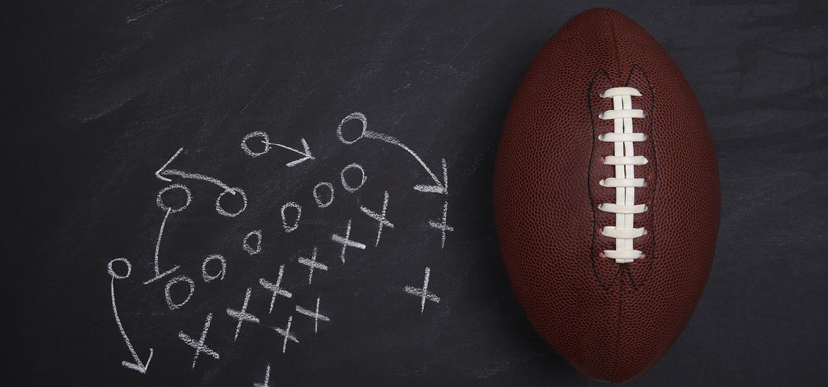 Xs and Os drawn in chalk on a blackboard in the form of a football play. A football is next to the drawing.