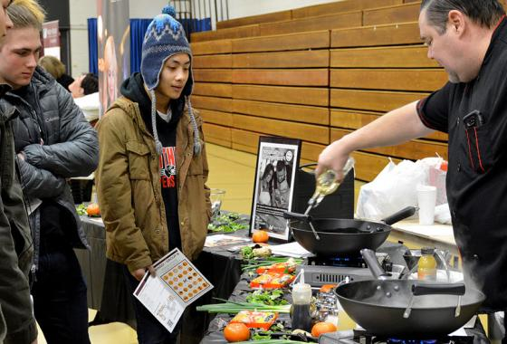 Mid-State Hospitality Management Instructor Paul Kennedy demonstrates his technique for cooking Orange Chicken during a high school outreach event on the College's Wisconsin Rapids Campus.